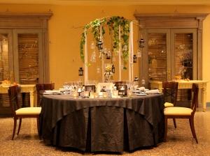 Composición de mesa con cubre mantel y faldón gris con sillas en cerezo barnizado y asiento acolchado color vainilla envuelto en luz cálida vista plano general