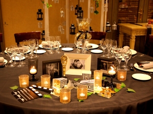 Mesa para boda en diseño cinéfilo con mantel gris oscuro, accesorio dorados, y retratos de actores vista angulo picado