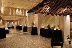 Recepción nupcial para asistentes y más allegados formado por mesas altas vestidas con faldones negros