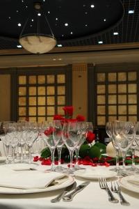 Rosal rojo como centro de mesa en contraplano con copas de cristal