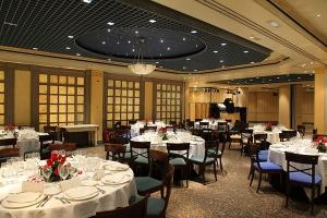 Salón para banquete nupcial decorado con rosas rojas, mesas en blanco y sillas cerezo con asientos en verde esmeralda vista en plano americano