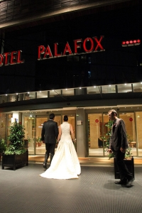Recién casados en la entrada del hotel Palafox con vista normal cubiertos en la magia del hotel