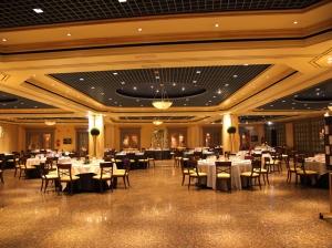 Espacio banquete con mesa presidencial al fondo rodeada por invitados envuelto en un ambiente cálido y estrellado en plano medio largo