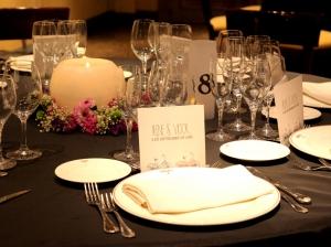Mesa para invitados con velón circular central sobre una base de flores coloridas con vista en primerísimo plano