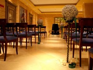 Ceremonia civil con altar nupcial al fondo y sillas de invitados en cerezo y asientos en azul marino