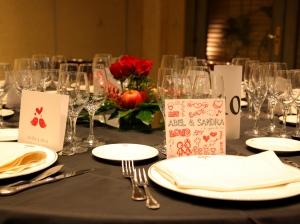 Mesa de allegados con manzanas y rosas rojas como centro de mesa