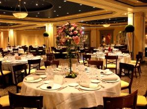 Mesa invitados en primer plano con decoración floral colorida en el centro