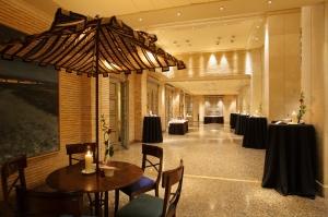 Espacio ambientado de recepción para invitados compuesto por mesa, sillas y sombrilla color cerezo con recibidores altos de faldón negro decorado con rosas rosas