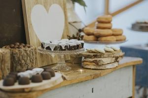 Brownies de chocolate y nueces bañados en chocolate blanco sobre tartera stand de vidrio transparente en vista plano medio corto
