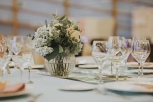 Rosas blancas en florero de vidrio transparente sobre mesa en vista en plano medio